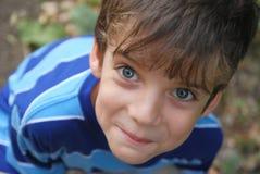 Ragazzo sorridente 7 anni, esaminante lo. immagine stock