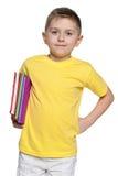 Ragazzo sorridente in camicia gialla con i libri Fotografia Stock Libera da Diritti