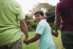Ragazzo sorridente che cammina con il padre ed il nonno al parco Fotografia Stock Libera da Diritti