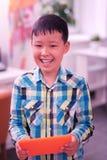 Ragazzo sorridente che gioca con la sua compressa arancio fotografie stock
