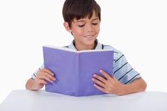 Ragazzo sorridente che legge un libro Fotografie Stock Libere da Diritti