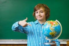 Ragazzo sorridente che mostra sul globo sopra il fondo della lavagna Concetto della scuola ed educativo Immagini Stock Libere da Diritti