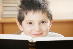 Ragazzo sorridente che osserva sopra il libro Fotografie Stock Libere da Diritti