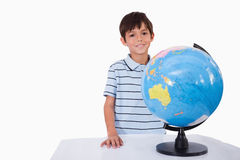 Ragazzo sorridente che posa con un globo Immagini Stock Libere da Diritti
