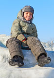 Ragazzo sorridente che si siede alla neve Fotografia Stock