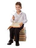 Ragazzo sorridente che si siede sul mucchio di vecchi libri con la lente Immagine Stock