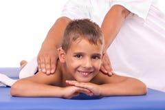 Ragazzo sorridente che si trova sulla tabella di massaggio Immagine Stock Libera da Diritti