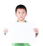 Ragazzo sorridente che sta con la carta in bianco orizzontale vuota in mani isolate su fondo bianco Immagini Stock