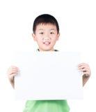 Ragazzo sorridente che sta con la carta in bianco orizzontale vuota in mani isolate su fondo bianco Fotografia Stock