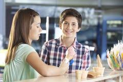 Ragazzo sorridente che sta con la sorella crema di Holding Strawberry Ice fotografia stock