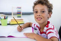 Ragazzo sorridente che studia allo scrittorio dentro in aula Fotografia Stock Libera da Diritti