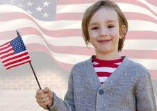 Ragazzo sorridente che tiene una bandiera americana per la festa dell'indipendenza Fotografia Stock