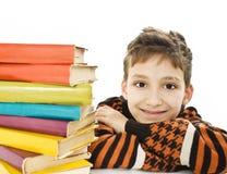 Ragazzo sorridente con i libri di banco sulla tabella Immagine Stock Libera da Diritti