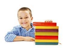 Ragazzo sorridente con i libri di banco sulla tabella Fotografie Stock