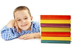 Ragazzo sorridente con i libri di banco sulla tabella Immagine Stock