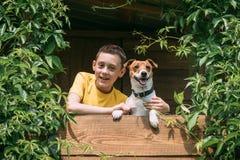Ragazzo sorridente con il cane sulla capanna sugli'alberi Fotografie Stock