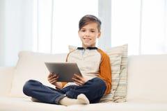 Ragazzo sorridente con il computer della compressa a casa Immagini Stock Libere da Diritti