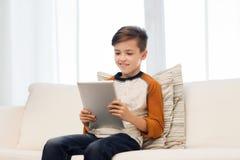 Ragazzo sorridente con il computer della compressa a casa Immagine Stock