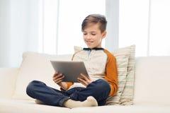 Ragazzo sorridente con il computer della compressa a casa Fotografia Stock Libera da Diritti