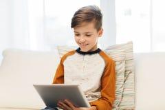 Ragazzo sorridente con il computer della compressa a casa Fotografie Stock Libere da Diritti