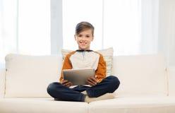 Ragazzo sorridente con il computer della compressa a casa Fotografia Stock
