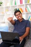 Ragazzo sorridente con il computer portatile che mostra i pollici in su Fotografia Stock