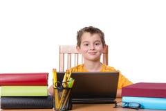 Ragazzo sorridente con il computer portatile ed i grandi libri Immagini Stock