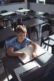 Ragazzo sorridente con il computer portatile ed il libro allo scrittorio Fotografia Stock Libera da Diritti