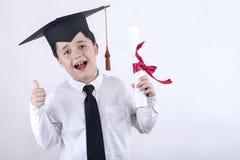 Ragazzo sorridente con il diploma nella graduazione Immagine Stock