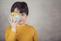 Ragazzo sorridente con un globo della terra che copre il suo occhio Fotografia Stock