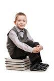 Ragazzo sorridente del bambino che si siede sui libri di lettura Fotografia Stock
