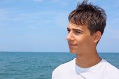 Ragazzo sorridente dell'adolescente contro il mare, osservante lontano fotografia stock