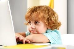 Ragazzo sorridente della testarossa che gioca con il computer Immagini Stock