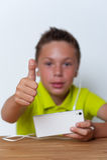 Ragazzo sorridente della Tween che per mezzo del suo smartphone Immagine Stock Libera da Diritti