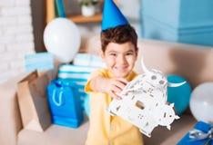 Ragazzo sorridente di compleanno che mostra il suo robot bianco del giocattolo Fotografie Stock