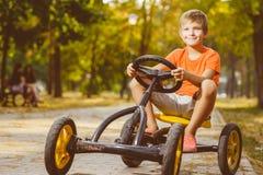 Ragazzo sorridente felice che conduce un'automobile del giocattolo all'aperto in Immagini Stock Libere da Diritti