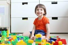 Ragazzo sorridente felice che gioca i blocchi di plastica a casa Fotografie Stock
