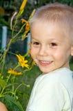 Ragazzo sorridente felice con i fiori gialli Fotografie Stock Libere da Diritti