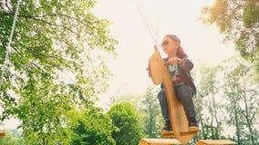 Ragazzo sorridente felice su un'oscillazione di legno sotto forma di cavallo in un parco alla luce solare Un bambino in occhiali  video d archivio