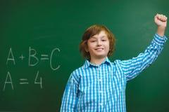 Ragazzo sorridente felice sul fondo della lavagna Concetto della scuola ed educativo Fotografia Stock