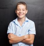 Ragazzo sorridente vicino alla lavagna Fotografie Stock