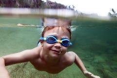 Ragazzo sotto acqua nel fiume Immagini Stock