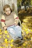 Ragazzo sotto l'albero di autunno Fotografia Stock