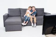 Ragazzo spaventato e ragazza che si siedono insieme sul sofà e sulla TV di sorveglianza immagine stock libera da diritti
