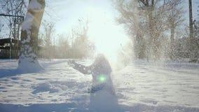 Ragazzo spensierato che gioca nella neve Gioco di vacanza invernale dei bambini al rallentatore Gioco della neve di divertimento  stock footage