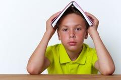 Ragazzo stanco che si siede alla tavola con il libro sulla testa Immagine Stock Libera da Diritti