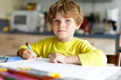 Ragazzo stanco del bambino a casa che fa le lettere di scrittura di compito con le penne variopinte Fotografia Stock Libera da Diritti