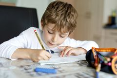 Ragazzo stanco del bambino a casa che fa le lettere di scrittura di compito con le penne variopinte Immagini Stock Libere da Diritti