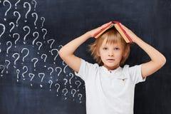 Ragazzo stanco e confuso di età di scuola primaria con Immagini Stock Libere da Diritti