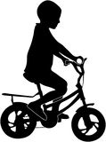 Ragazzo su una siluetta della bici Fotografia Stock
